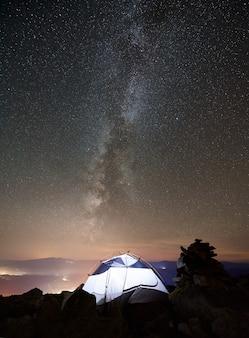 Campo turistico sulla cima della montagna sotto il cielo stellato notturno