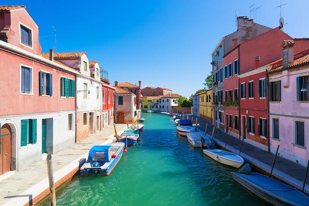 Canale dell'isola di murano, case variopinte e barche durante il giorno di estate con cielo blu in italia.