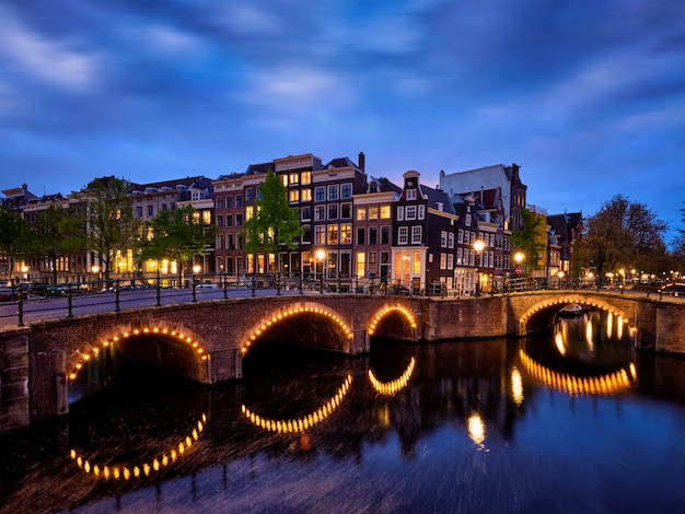 Canale di amsterdam, ponte e case medievali la sera