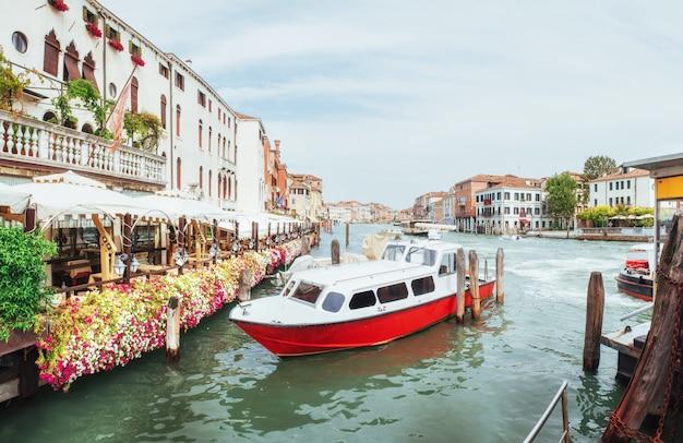 Canale idrico verde con le gondole e le facciate variopinte di vecchie costruzioni medievali al sole a venezia