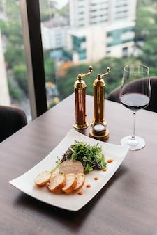 Canape con paté di foie gras e insalata servita con vino bianco.