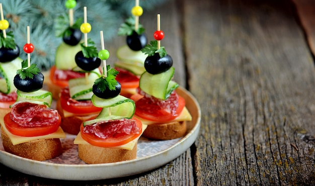 Canape di natale su spiedino di pane baguette con toast formaggio, salsiccia, pomodoro, cetriolo e olive.