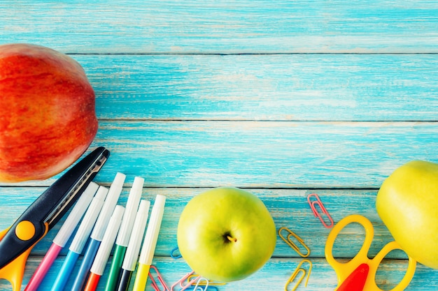 Cancelleria della scuola, strumenti dell'ufficio e mele sulla vista superiore del nackground di legno blu
