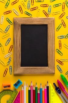 Cancelleria e lavagna variopinte della scuola su fondo di carta giallo