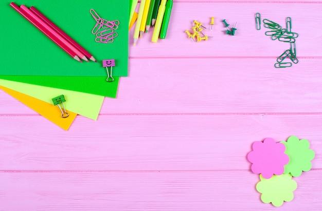 Cancelleria gialla e verde e feltro su fondo di legno rosa.
