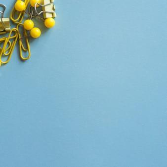 Cancelleria giallo e acciaio sul tavolo blu