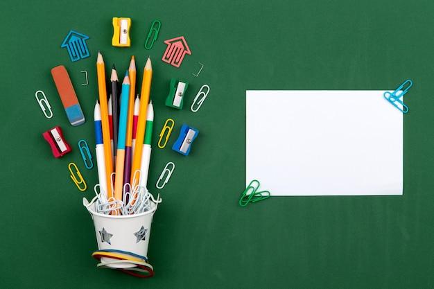 Cancelleria matite cancelleria penna gomma in un secchio bianco. natura morta sul fondo del consiglio scolastico verde. copia spazio piatto posare vista dall'alto concetto educazione