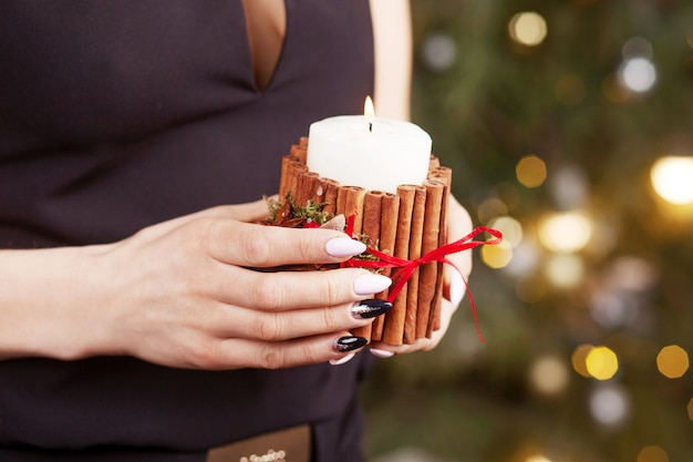 Candela accesa nelle mani di una ragazza. candela di natale. decorazioni natalizie. le mani della donna che tengono bella candela con fuoco. copia spazio