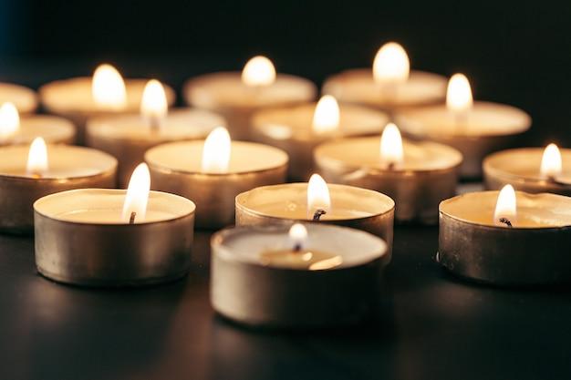 Candela accesa sul tavolo nelle tenebre, spazio per il testo. simbolo funebre