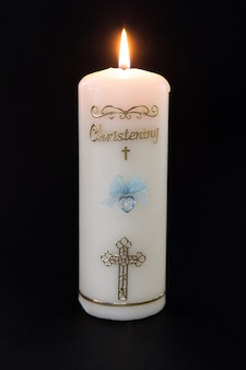 Candela battesimale bianca accesa con dettaglio blu