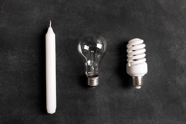 Candela bianca e lampadine elettriche sui precedenti neri