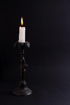 Candela bianca in candeliere d'epoca su sfondo nero