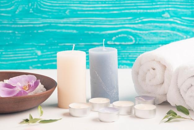 Candela con asciugamano arrotolato e stecca spa con fiore orchidea sulla scrivania