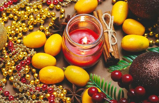 Candela, decorazioni natalizie, cannella e kumquat