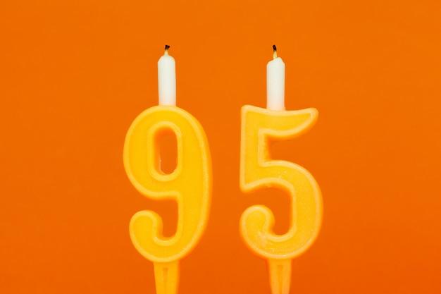 Candela di compleanno di cera colorata su sfondo arancione
