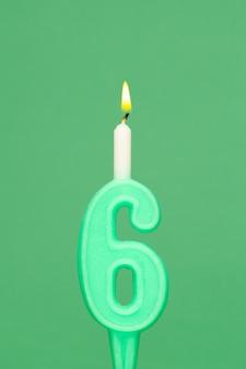 Candela di compleanno di cera colorata su sfondo verde