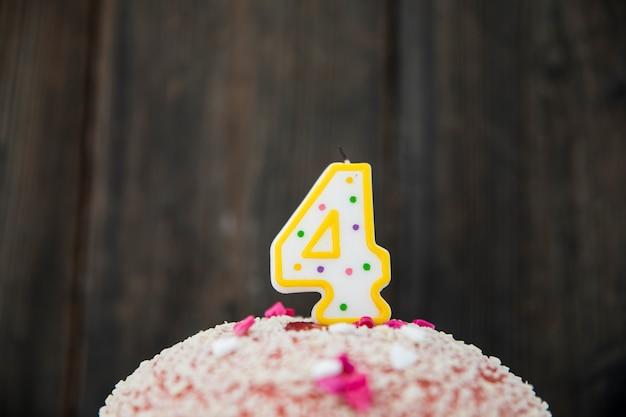 Candela di numero 4 in una torta di compleanno contro fondo di legno blu
