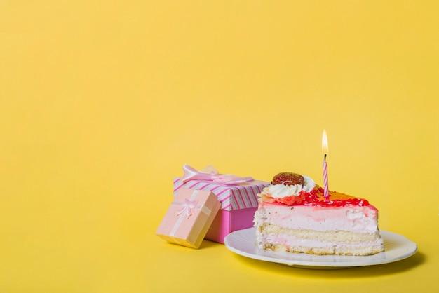 Candela illuminata sul dolce fetta con due scatole regalo contro sfondo giallo