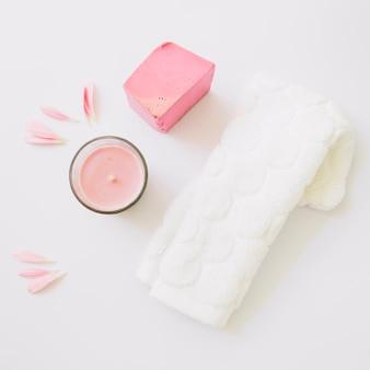 Candela; petali di gerbera; saponetta e tovagliolo bianco isolato su sfondo bianco