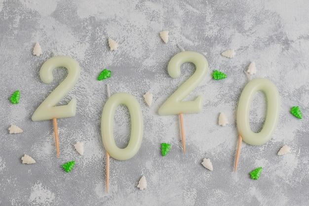 Candele a forma di numeri 2020 come simbolo del nuovo anno accanto a caramelle scintillanti a forma di natale su un tavolo grigio. vista dall'alto, piatto