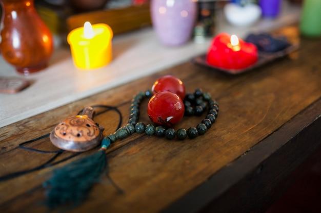 Candele accese con sfere cinesi rosse; perle di tartaruga e preghiera per il relax sulla scrivania di legno