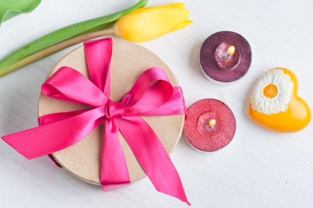 Candele accese e confezione regalo con nastro rosso