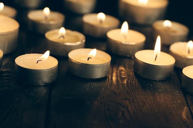 Candele accese nell'oscurità sul nero. concetto di commemorazione.