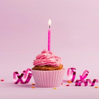 Candele accese sopra i muffin con codette e stelle filanti su sfondo rosa