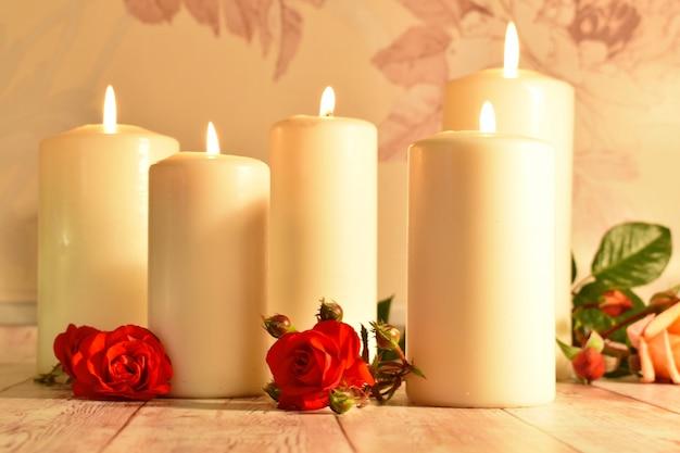 Candele bianche e germogli di rosa rossa su legno