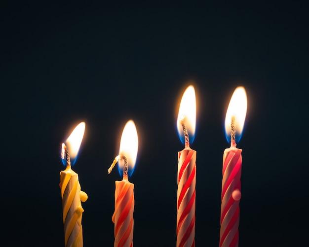 Candele brucianti di compleanno su fondo scuro con fuoco.
