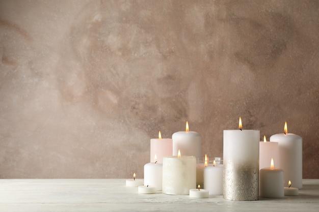 Candele brucianti sulla tavola di legno bianca su marrone