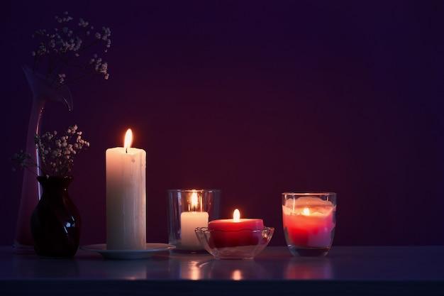 Candele con fiori sul tavolo di legno bianco su sfondo viola