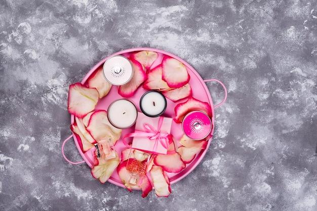 Candele con petali di rosa sul vassoio rosa, cosmetici e scatola regalo su sfondo grigio pietra