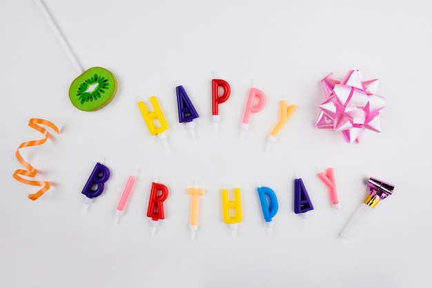 Candele di buon compleanno con oggetti colorati