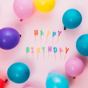 Candele di testo di buon compleanno con bastone e palloncini su sfondo rosa