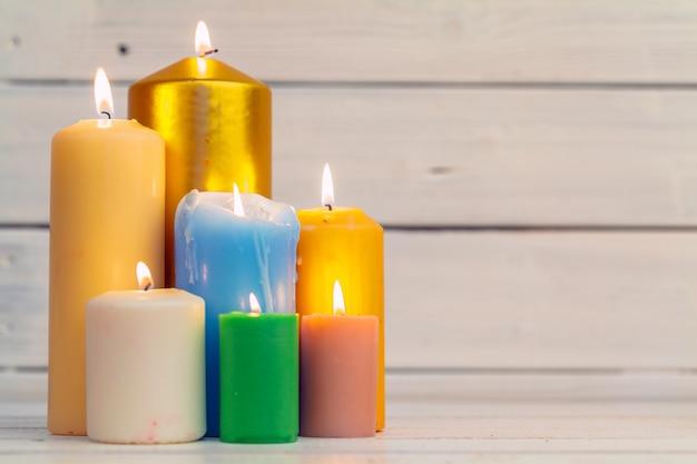 Candele domestiche di illuminazione sulla tavola di superficie di legno