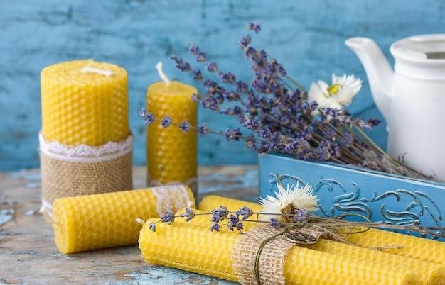 Candele fatte di cera naturale, in una scatola di legno, fatte per le vacanze. la candela è fatta a nido d'ape.