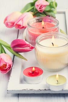 Candele gialle e rosa dell'aroma con i tulipani