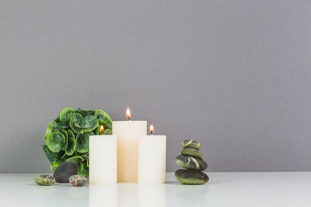 Candele illuminate; pietre spa e foglie verdi di fronte al muro grigio