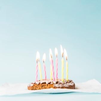 Candele illuminate sulla torta cotta con la carta velina contro fondo blu