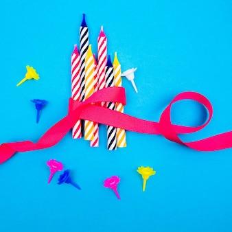 Candele variopinte a strisce per la festa di compleanno su fondo bianco. distesa piatta.