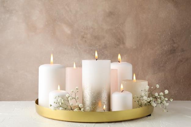 Candele, vassoio e fiore brucianti sulla tavola bianca