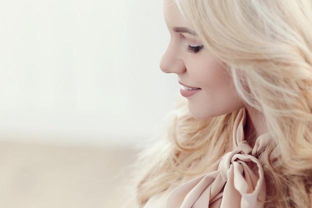 Candida bella donna bionda con capelli ondulati, profilo o vista laterale