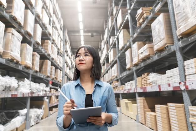 Candido del giovane revisore della donna asiatico attraente o del personale dell'allievo lavoro che cerca inventario di inventario.