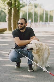 Cane guida che aiuta un cieco in città. bel ragazzo cieco riposare con il golden retriever in città.