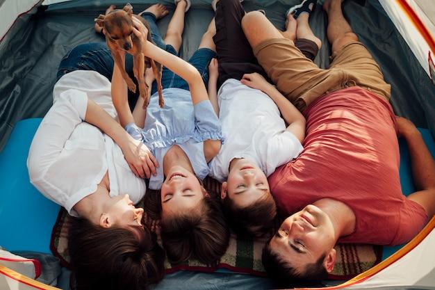 Cane sorridente della tenuta della ragazza mentre i suoi genitori e fratello che dormono in tenda