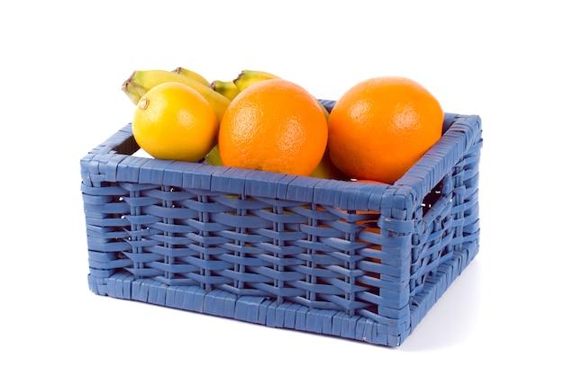 Canestro blu con i frutti su fondo bianco