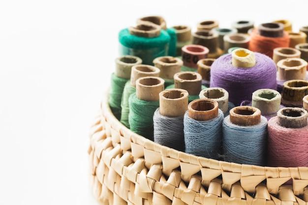Canestro con i fili per cucire su fondo bianco