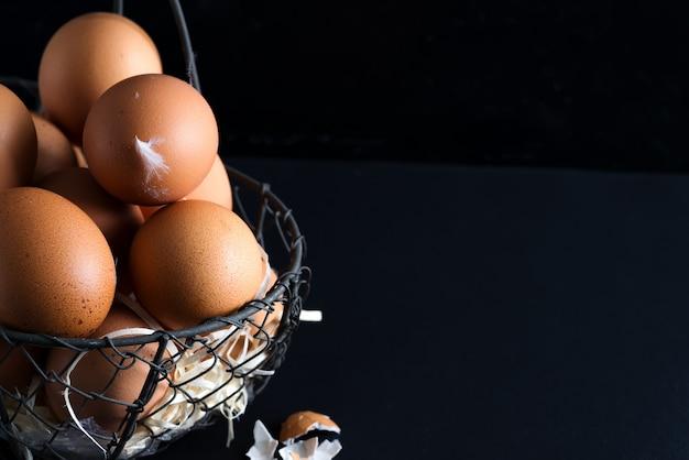 Canestro con la fine sulle uova di pollo naturali dell'azienda agricola fresca su un fondo nero. carta di congratulazioni di pasqua.