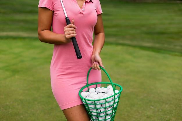 Canestro da golf della tenuta della ragazza del primo piano